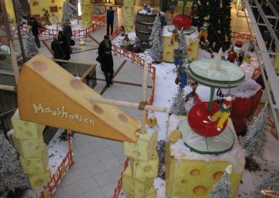Entrance gate to Micetown made of pieces of cheese and a cable car made of cucumber slices in the Europacenter