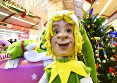 Weihnachtself schaut Kunden an / Christmas elf looks at customers