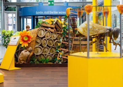 Glaswabe mit Biene und Bienenstock im Hintergrund
