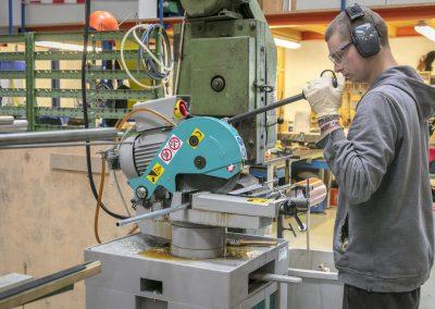 Ein Mitarbeiter der Abteilung Mechanik sägt ein Bauteil für eine Figur zu.