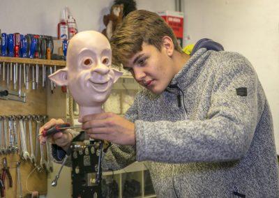 der junge Mechaniker nimmt eine Feineinstellung an einer beweglichen Figur vor.
